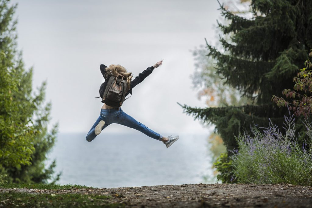 Girl hiking outside jumping
